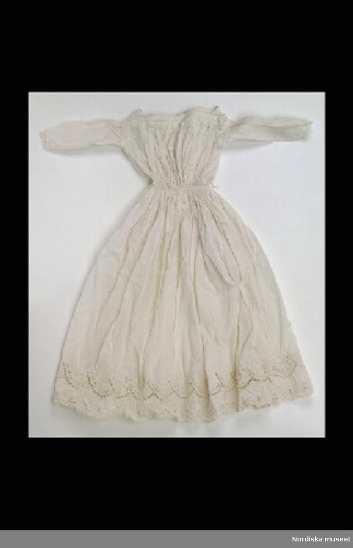 Inventering Sesam 1996-1999: L 47 (cm) Klänning, dockklänning, av vitt bomullstyg (linong), rak halsringning, lång ärm, vid rynkad kjol med dragsko i midjan och brodyr nedtill.  Anna Womack jan. 1997