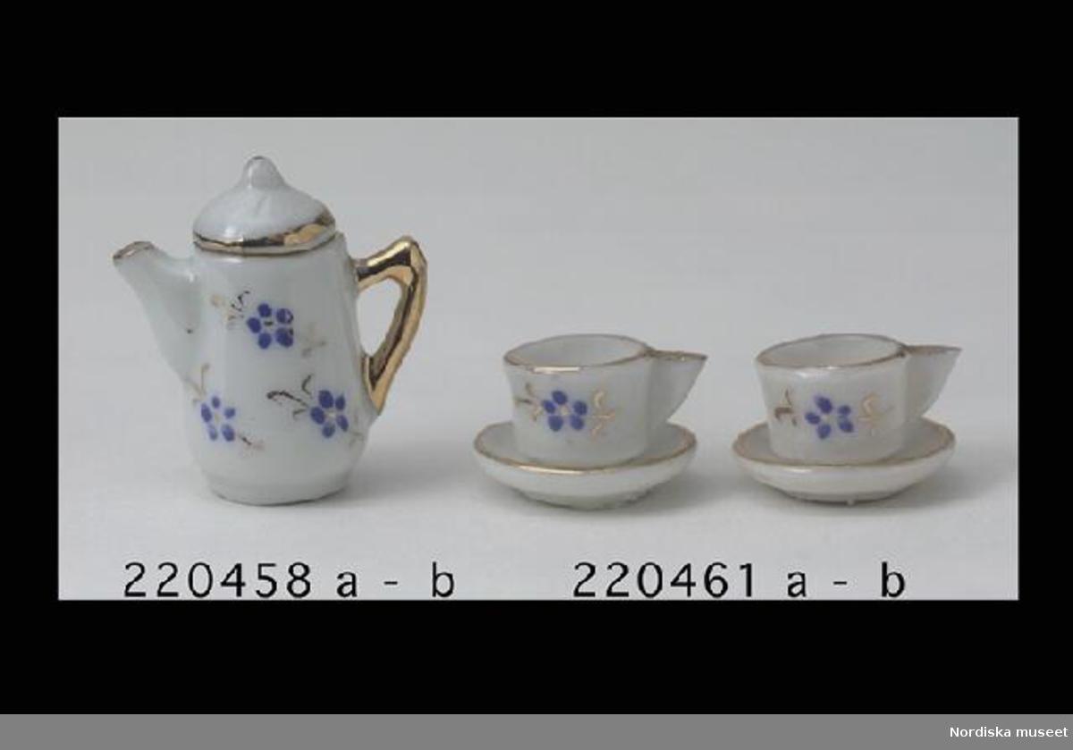 Inventering Sesam 1996-1999: H 1,3 cm Diam 2,1 cm Två kaffekoppar med fat a:1-2, B:1-2, till dockskåp, av vitt porslin med målad blå blomma och förgyllning. Brukad av Catarina (född 1919) och Anne-Sophie (född 1921) von Heidenstam, döttrar till givaren. Tillhör dockskåp 220.405 med inv nr 220.406-220.760 Helena Carlsson 1997