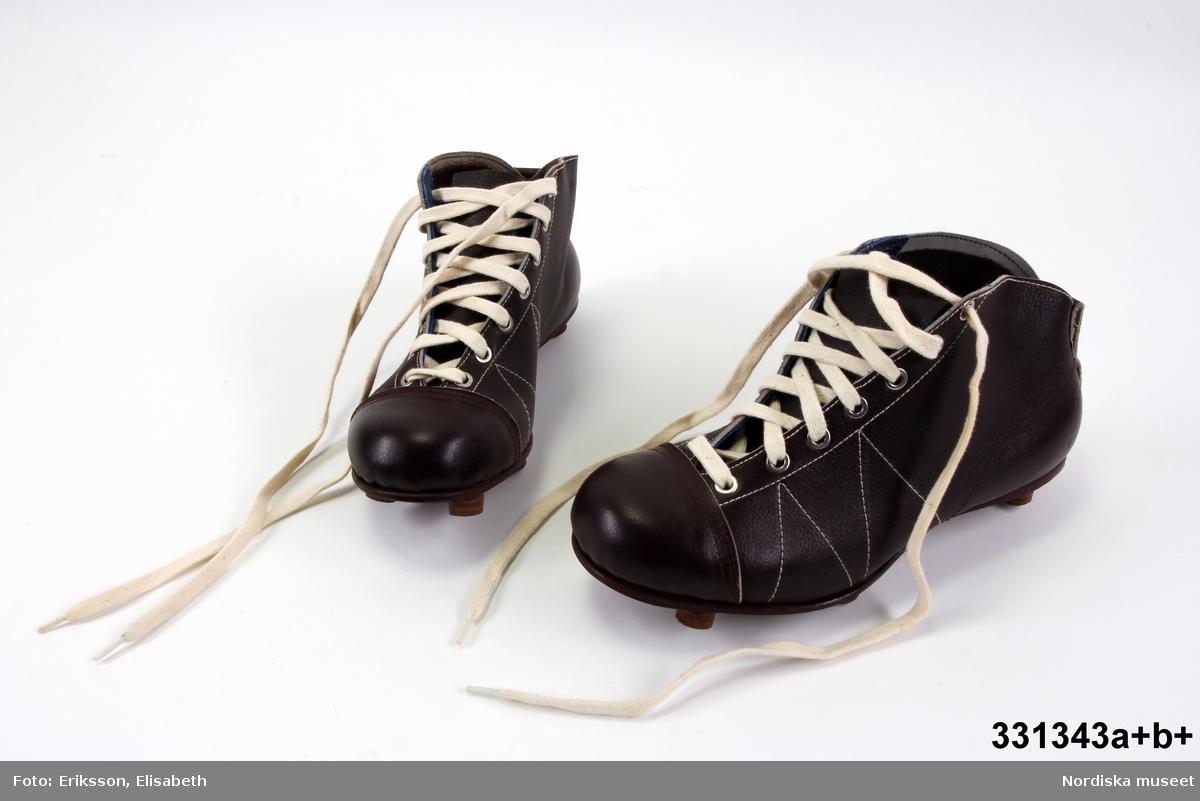 """Ett par bruna fotbollsskor av kraftigt läder, modell """"Club"""", tillverkade av Hults, storlek 41. Snörning med vita skosnören genom metallförsedda hål.  Vita sömmar och rundad tå. Läderpiggar på undersidan. Spikad lädersula. /Karin Dern 2012-06-04"""