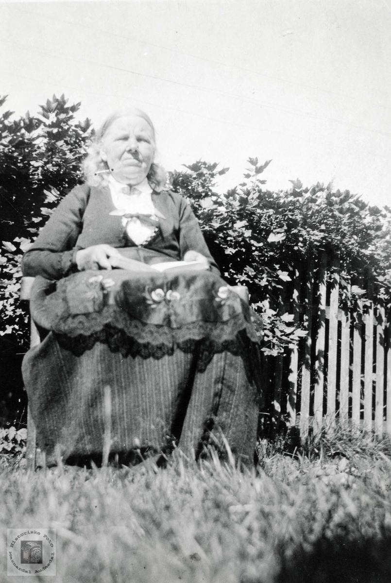 Ingrid Ubostad, f. 1846, har tid til ei lesestund i hagen på Ubostad. Grindheim Audnedal.