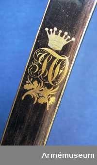 Grupp D II  Tregrenighet, förgyllt mässingsfäste, kaveln klädd med svart skinn, lindad med två tvinnade mässingstrådar. Bakre parerstången utformad som ett bockhuvud. På styrskenorna Fortifikationsemblemet. Klingan krökt och eneggad, upptill blonerad med förgylld dekor, där Carl XIV Johans och kronprins Oscars namnchiffer samt norska och svenska riksvapnen ingår.   Samhörande nr är AM.45212-13