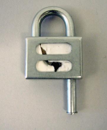 Hänglås med tillhörande två nycklar (passar även till PM 17184). Låshuset är i mässing och låsbygeln samt fronten är i stål. Låset är så konstruerat att en papperslapp med signatur och datum placeras inne i låset när väskan försluts. På så sätt kan man se om låset brutits.