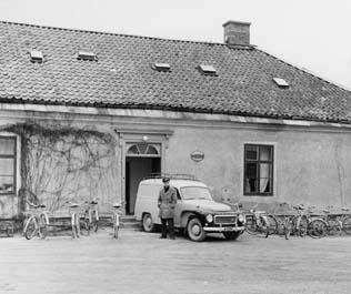 Postkontoret Djursholm 2, Östra slottsflygeln. Framför entrén förste postiljon Assar Svensson. Bilen är en Volvo Duett, årsmodell 1960-1962.