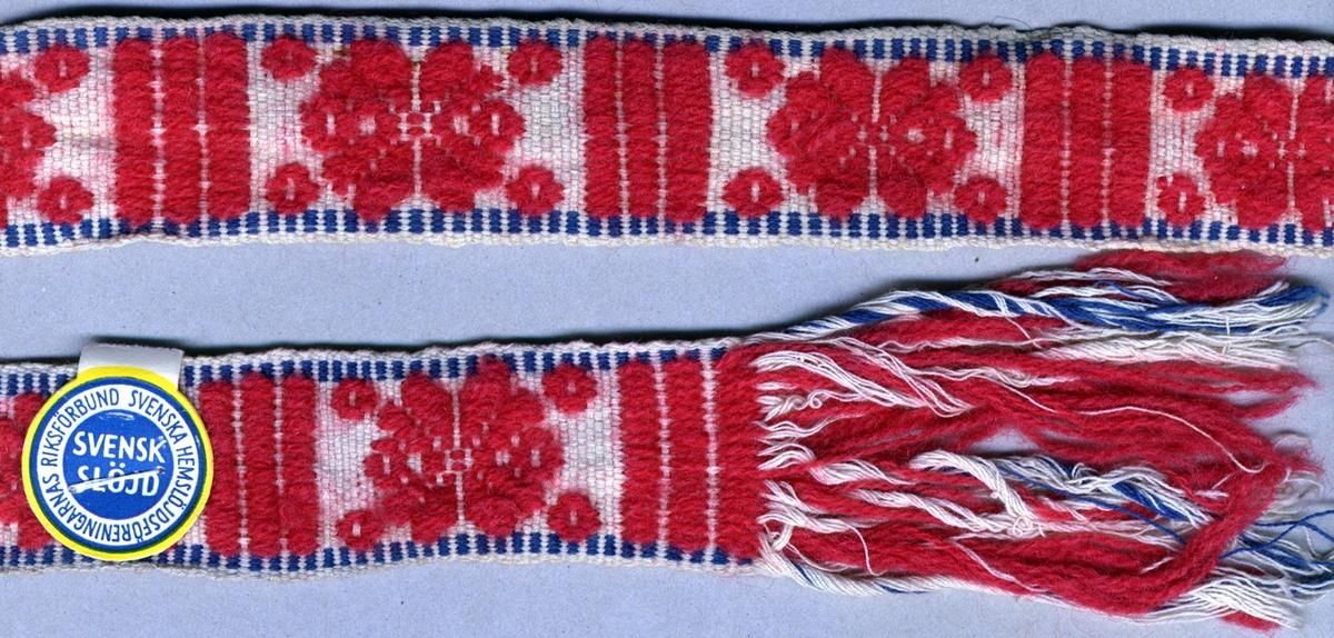 """Livband vävt i varprips med plockat mönster. Mittfältet är mönstrat med röda stjärnor och ränder på vit tuskaftsbotten. Kantat med en blå-vit tvistrand längs vardera sidan. Frans av varptrådarna i var ände, ca 80 mm lång. Varp i vitt och blått 2-trådigt s-tvinnat bomullsgarn, två trådar tillsammans, samt i rosarött 2-trådigt s-tvinnat ullgarn. Inslag i vitt 2-trådigt s-tvinnat bomullsgarn, fyra trådar tillsammans. Längd inklusive fransar.Märkt med en SHR-etikett med påskriften: """"Nr 20"""". Bandet är också märkt med ett påsytt band med invävd text: """"SVENSK SLÖJD Malmöhus hemslöjd MALMÖ""""."""