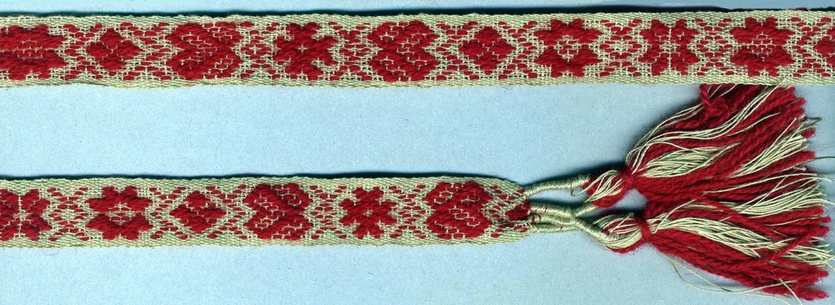 """Livband med plockat krabbasnårsmönster med rda stjärnor, hjärtan med krokar och dubbelkors på oblekt tuskaftsbotten. Avslutat i var ände med två tofsar (60 mm långa); varptrådarna är först omlindade med oblekt garn vari extra trådar till tofsen är iknutna i varpgarnets färger.Varp i oblekt 2-trådigt s-tvinnat lingarn och rött 2-trådigt s-tvinnat ullgarn. Inslag i oblekt 2-trådigt s-tvinnat lingarn.Längd inklusive fransar. Märkt med ett påsytt band med invävd text: """"SVENSK SLÖJD Malmöhus hemslöjd MALMÖ""""."""