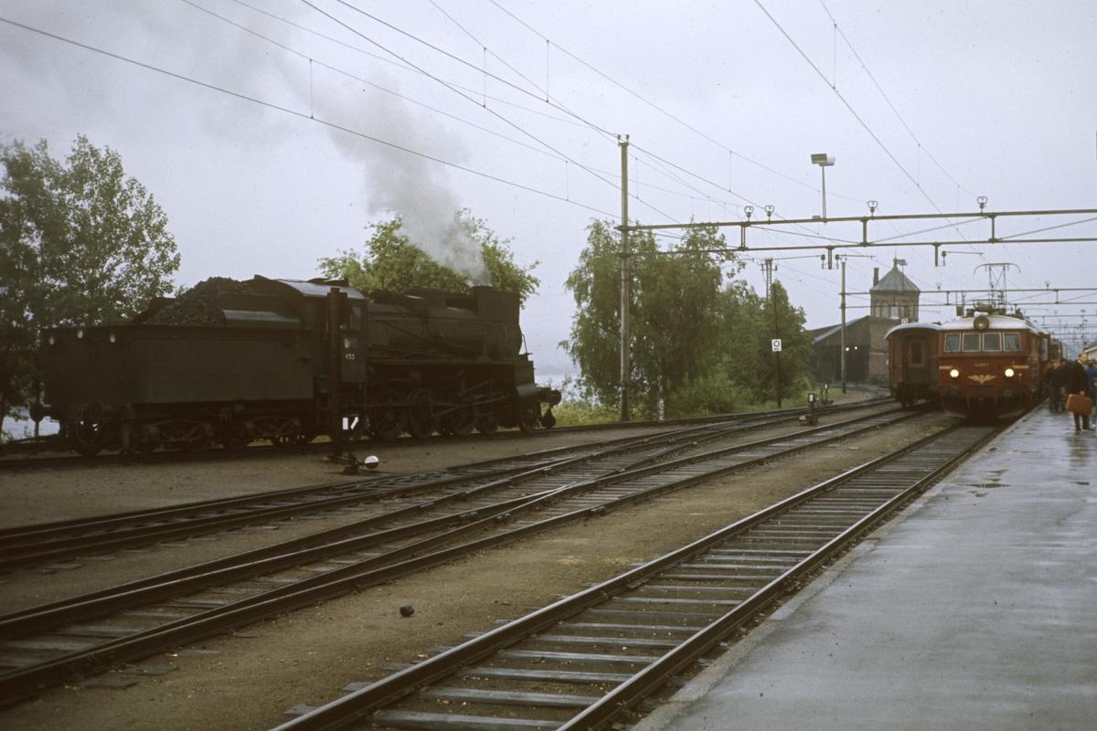 Damplok type 26c nr. 433 på Kongsvinger stasjon. Persontog til Oslo Ø. står ved plattformen.