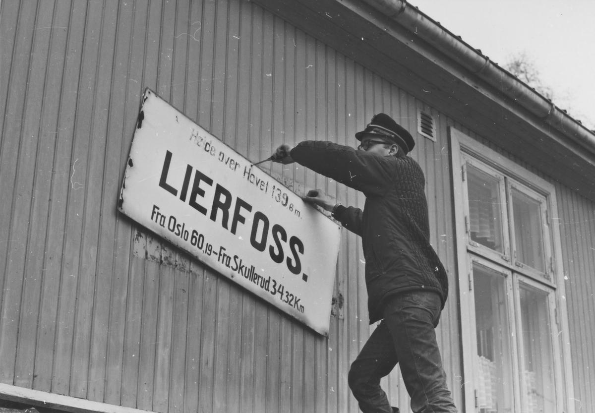 Fra Lierfoss stasjon noen år etter nedleggelsen. Stasjonsskiltet demonteres for overføring til museumsbanen.