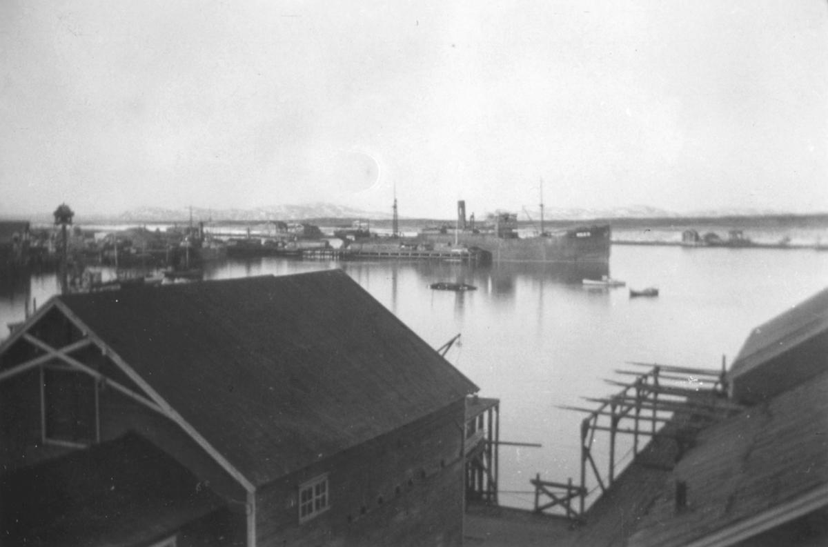 Utsikt over havna i Vadsø. I forgrunnen ses havnebygninger. 'Akka' et skip i tysk fart ligger til kai. Bildet er tatt fra 2.etasje i Evangergården i Havnegaten