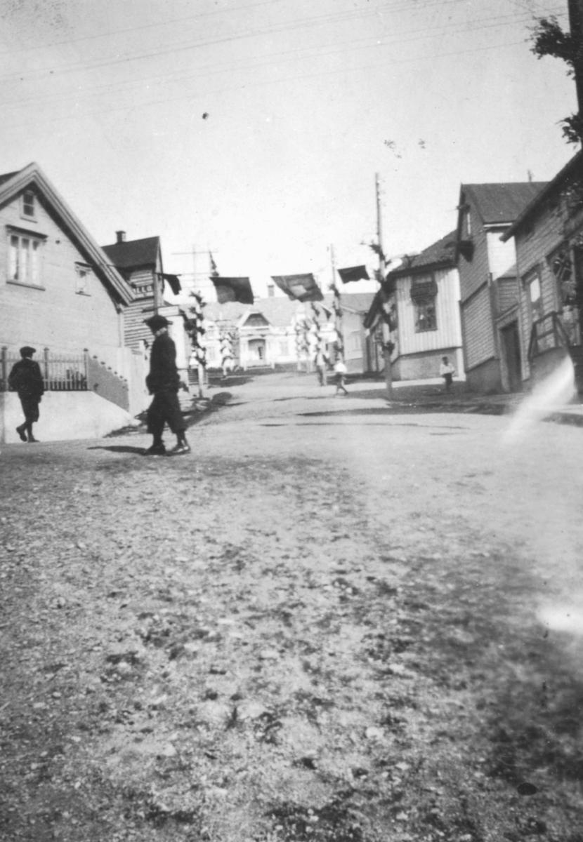 Tollbugaten i Vadsø sett mot Fylkesmanngården. Den er pyntet til Kong Haakons besøk, sommeren 1922. Over og langs gaten, henger det flagg. I forgrunnen går det to menn i mørke klær