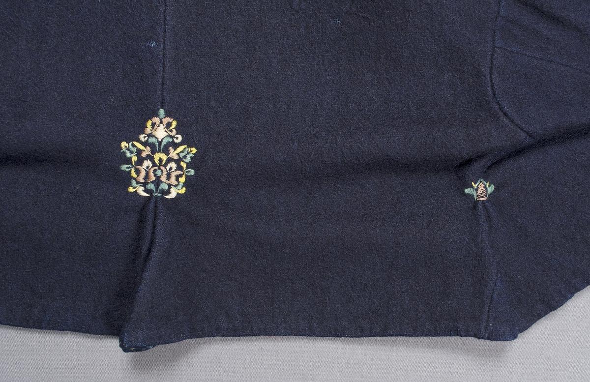 Mörkblå vadmalströja garnerad med band och broderier. Tröjan har en rund öppning fram, strax under halsringningen, och skört bak. Tröjan är dekorerad med ett 36 mm brett ljusare blått sidenband längs halsringning och öppningen fram samt längs nederkanten på framstycken och ärmar. Vid ärmens nederkant är dessutom ett 30 mm brett mönstrat band påsytt mitt emellan två blå sidenband, bandet har svart sammetsbotten med blommönster i rosa och grönt silke. Broderier i plattsöm och flätsöm på framstyckena, på och intill sidenbandet, samt på bakstycket vid skörtsömmarna. Broderiet föreställer blommor, blomsterurnor och spiror och är sytt med silke i grönt, gult och rosa. Framtill knäpps tröjan på två ställen med en hyska och hake. Söm mitt bak, skörtflik nedtill, ytterligare en skörtflik bak intill vardera sidan. Axelbredd: 140 mm. Ena axeln är skarvad med en tygbit (i samma tyg). Ärmlängd: 500 mm. Ärmen är sydd i ett stycke med en kil. Ena ärmen är skarvad med en tygbit (i samma tyg).Ärmsprundet är 90 mm långt och knäpps med en hyska och hake. Tröjan är helfodrad med halvblekt handvävt linnetyg.