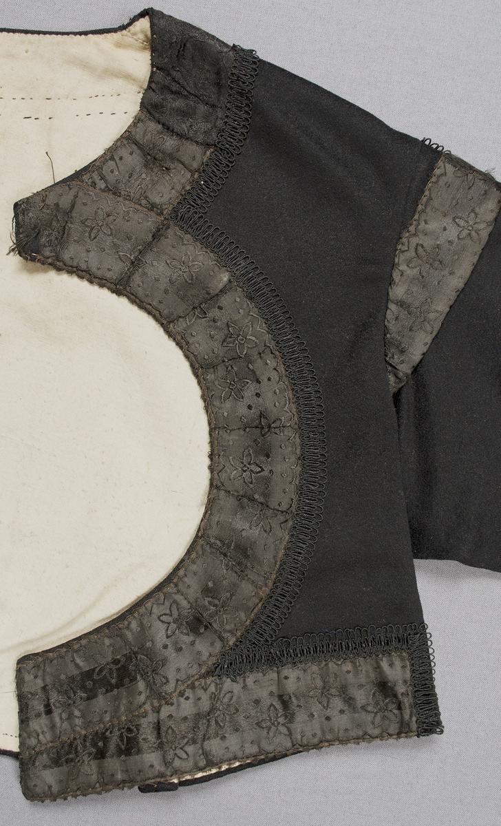 """Svart tröja i ylletyg garnerad med band. Tröjan har en rund öppning fram på bröstet, skört bak och karm på ärmarna.Tröjan är dekorerad med två olika, 33 mm breda, svarta mönstrade sidenband runt halsringning och öppningen fram, längs nederkanten på framstycken och ärmar samt i ärmkarmen. Intill sidenbandet på framstyckena sitter ett svart genombrutet, 12 mm brett garneringsband. Mellan de två svarta sidenbanden på ärmens nederkant är ett 40 mm brett mönstrat band påsytt, bandet har svart sammetsbotten och blommönster i rosa och grönt silke. Ovanför banden på ärmen sitter ett genombrutet garneringsband i svart och brunt, ovanpå detta löper en fastsydd tråd med glest trädda svarta pärlor. Framtill knäpps tröjan på två ställen med en hyska och hake. Söm mitt bak med ett skört nedtill, ytterligare en skörtflik på var sida. Broderier i plattsöm vid skörtsömmarna. Ärmlängd: 515 mm. Ärmen är sydd i ett stycke. Ärmsprundet är 105 mm långt och knäpps med en knapp och knapphål; runda svarta knappar med vitt """"öga"""", tränsat knapphål. Axelbredd: 130 mm. Axelkarmen är som bredast 40 mm.Tröjan är helfodrad med ett ljust tuskaftat bomullstyg."""
