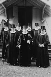 Gruppe 7 prester i flosshatter,prestekjole,Veldre kirke. T.h