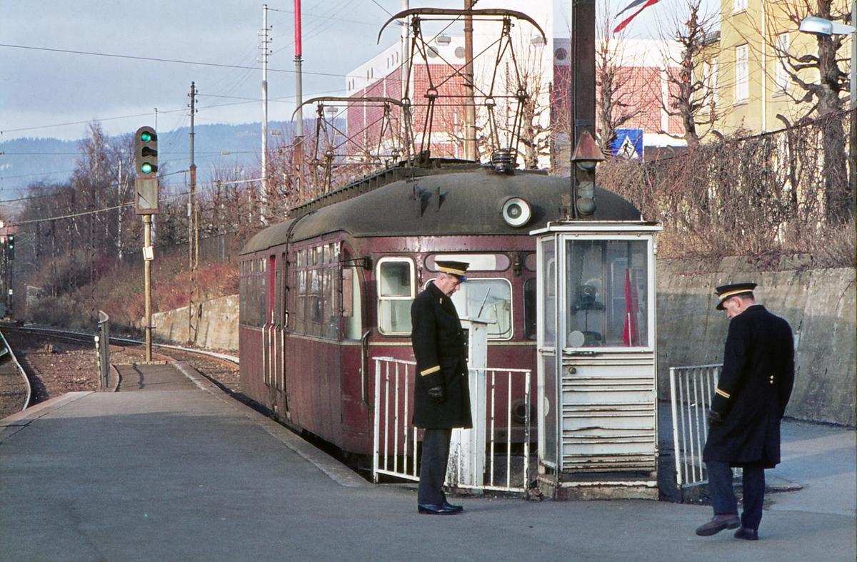 """A/S Holmenkolbanen. Majorstuen. Vogn 113, type 1939 (Skabo, NEBB). HKB kontrollører betjener stillverket. Ekstravogn til """"Setra"""" (Frognerseteren)."""