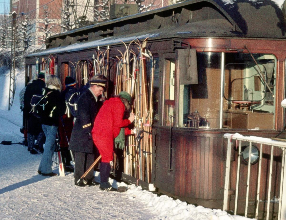 A/S Holmenkolbanen. Oslo Sporveier. Montering av ski på utvendige skistativ. Ekstravogn til Frognerseteren. Skistativet på venstre side var for reisende til Voksenkollen, som hadde egen plattform på venstre side. Vogn 203, type 1934.