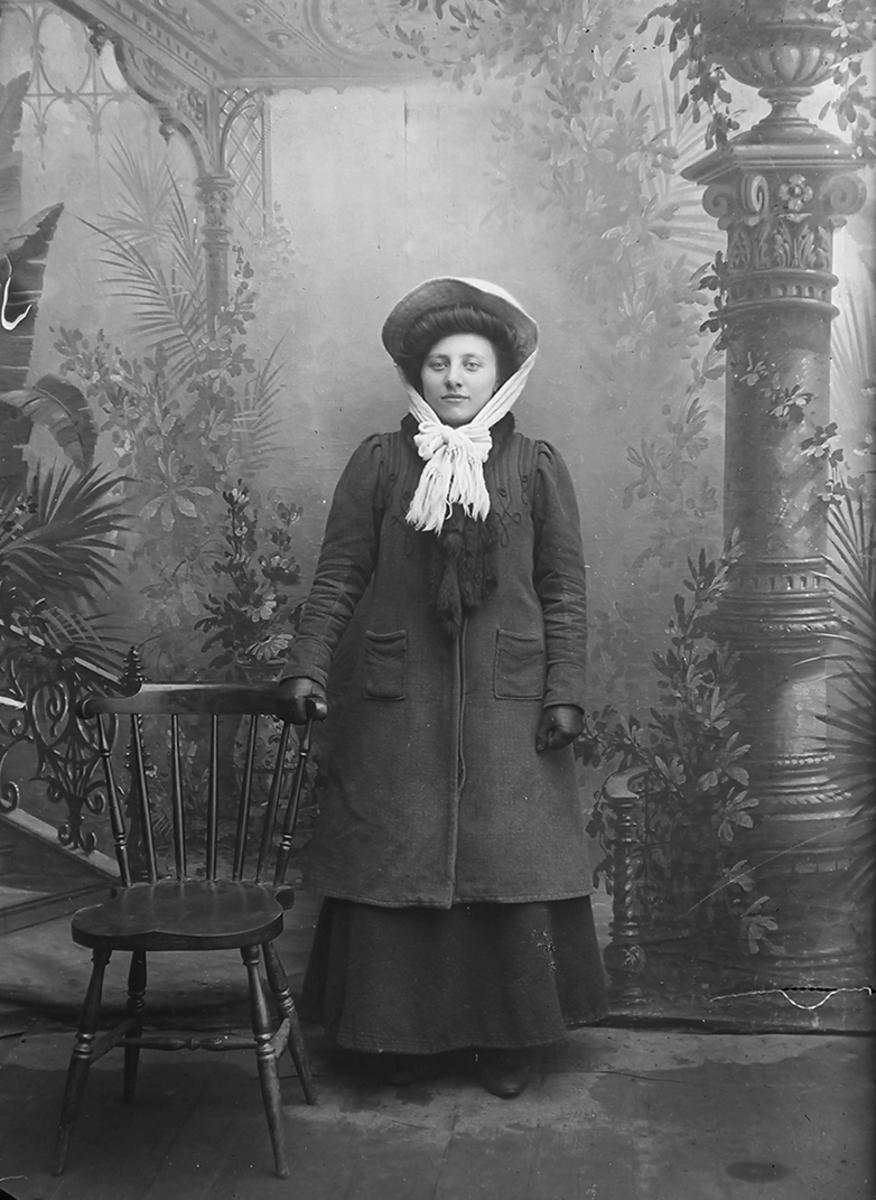 Portrett.Dame, står ved en stol. Hun har på seg ytterjakke, hansker, tørkle rundt halsen og hette på hodet.Bildet er tatt på Reine i Lofoten.
