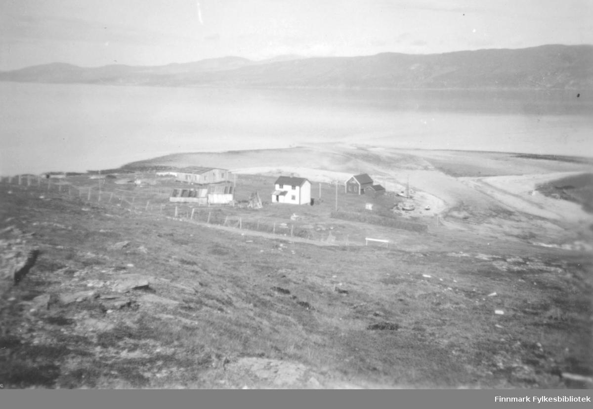 Kokelvmunningen til høyre i bildet. Til venstre nederst mot sjøen, ligger Svendsens gjennreisningsbrakke. Det hvite huset er boligen til Peder Nikodemussen, med fjøset oppfor. Et naust ligger nede ved vannet. Det er et gjerde rundt bebyggelsen