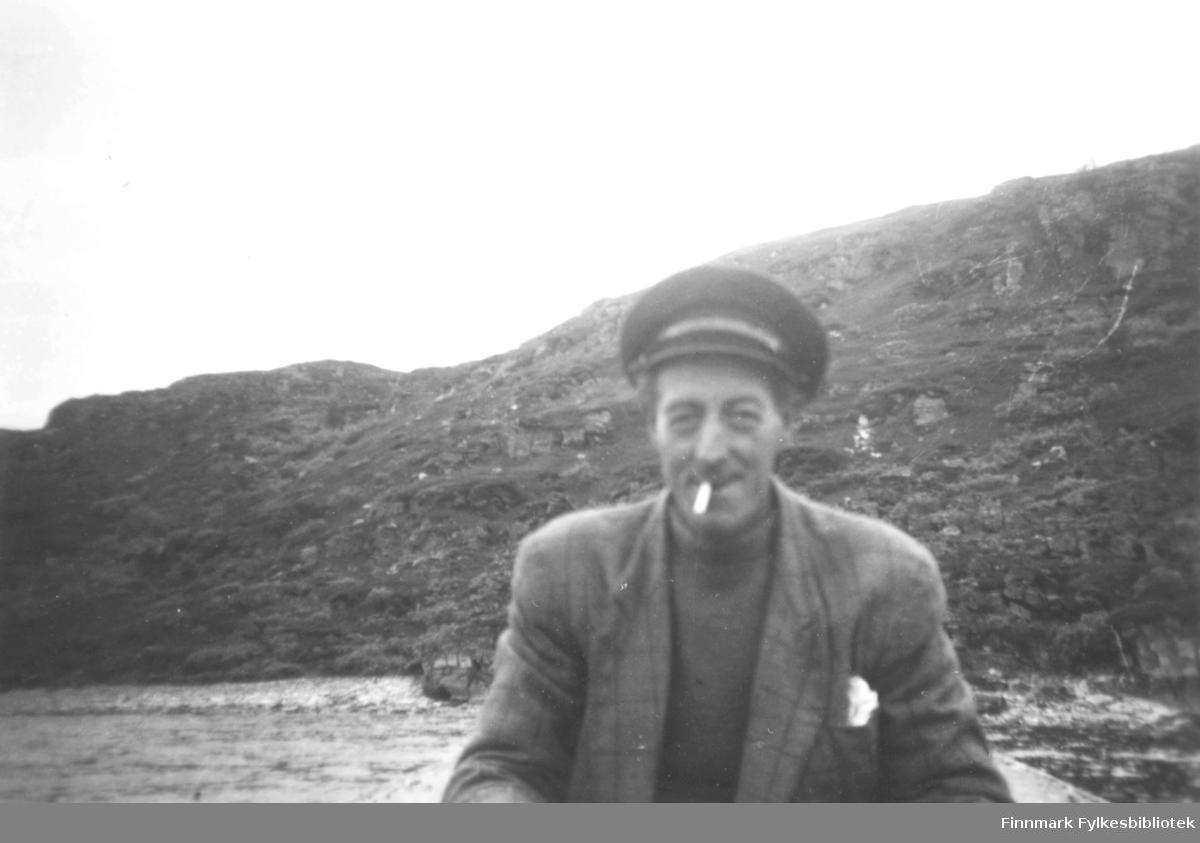 Skipper Nikolai. Han var skipper på båten 'Bankenes'. På bildet er han kledt i en rutete jakke, og høyhalset  genser. På hodet har han en skyggelue. I munnen har han en tobakksrøyk. Det er fjell i bakgrunnen