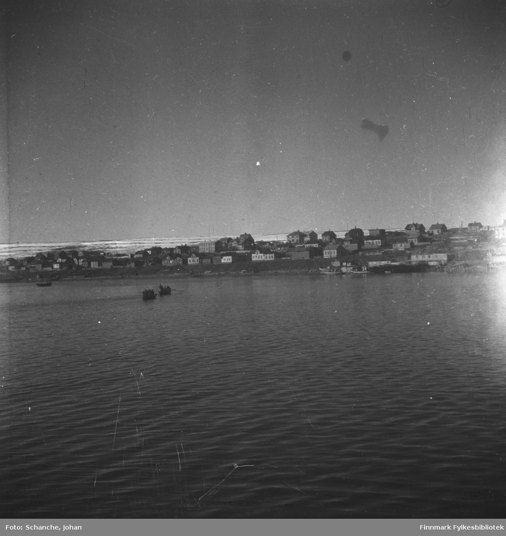 Indrebyen i Vadsø fotografert fra havet. To båter ror mot byen. Ruiner bland byggninger. Fjellen bak byen er delvis dekt av snø.