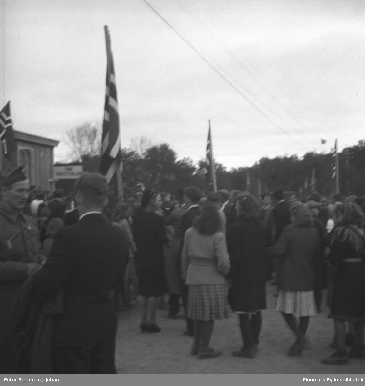Kongebesøk i 1946: Kong Haakon VII besøker Tana. Folkemengde står på gata foran Tana Turiststasjon, nesten alle med ryggen mot kamera. En soldat har snyd seg i rekka for og prate med en mann.
