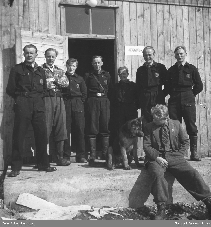 Åtte politimenn samlet til gruppebilde utenfor gamle politibrakke/sorenskriverkontor i Vadsø sommer -46.  To av dem er kledd i sivilklær. En av dem sitter på trappa, røyker sigarett og prater til en seferhund, som sitter ved siden av ham.  Ved døråpningen henger det et skilt med tekst:'sorenskriveren'. Fra venstre nr. tre Alfred Henriksen, nr. fire Bernhoff Andreassen og nr. syv Thor Wara. Dagen er solig og døren til politikammer står åpen.