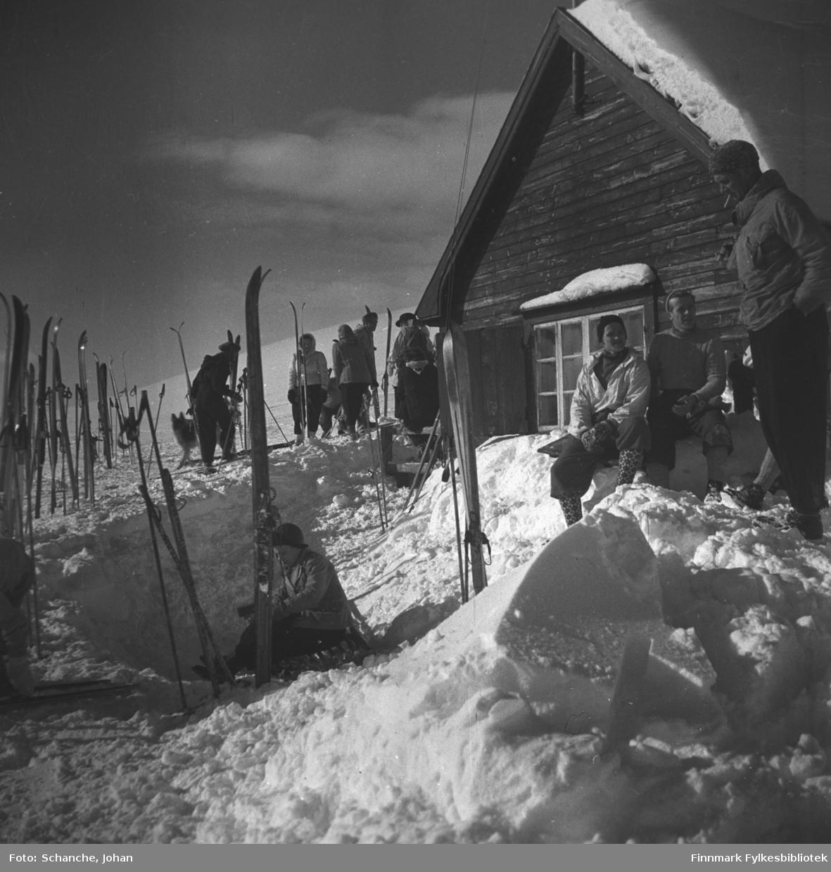 Vinikka skihytte fotografert en solig vårdag i 1946. Flere ski står oppstillt på snøen rund hytta. Folk i anorakk går bland skiene.  To menn sitter på snøen og soler seg, ved siden av dem står en mann og røyker.