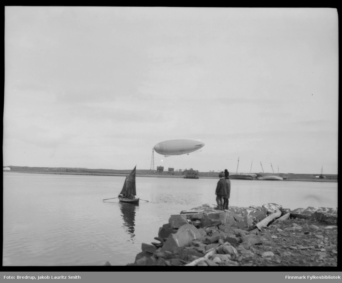Luftskipet Italia ankret opp ved luftskipsmasta på Vadsøya, mai 1928. Bildet er tatt på Ørtangen i Vadsø der to barn står og venter på fløttmannens båt.  Fløttmannen skysset folk fra Ørtangen til Øya.  I bakgrunnen ser man det enorme luftskipet som svever over Øya.  På øysiden ligger to vrak av russiske fartøyer i fjæra.