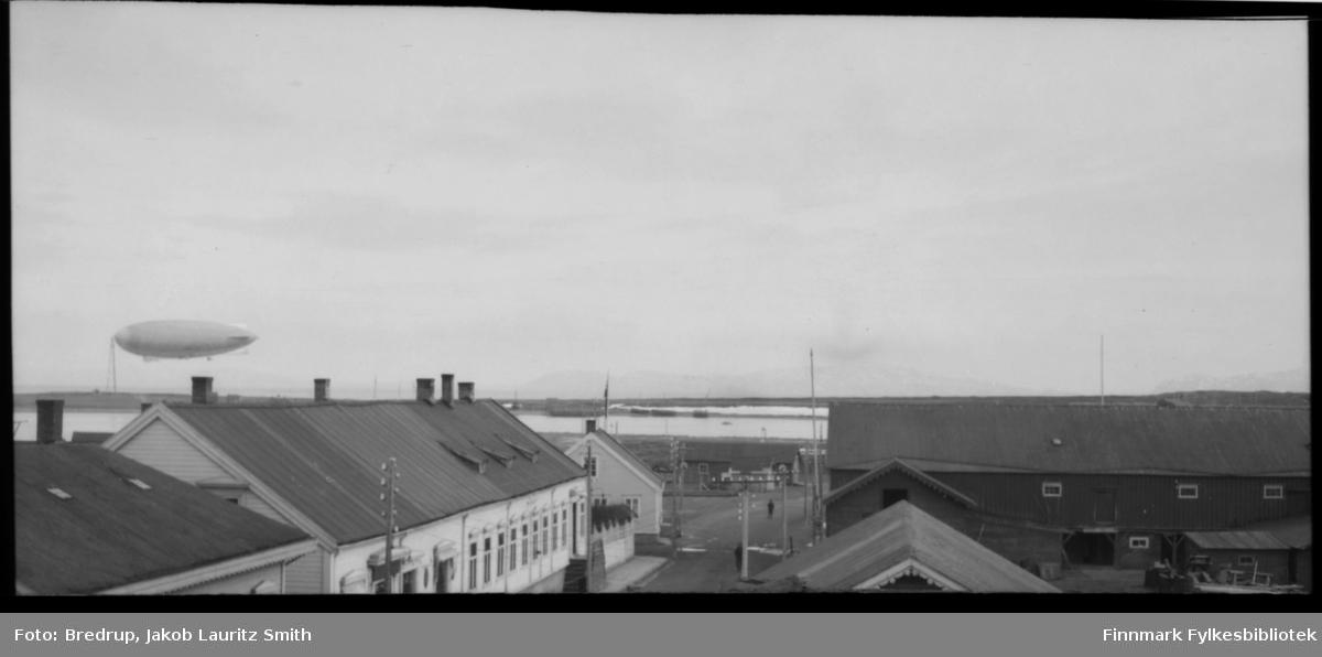 Luftskip forankret ved luftskipsmasta i Vadsø.  Bildet viser også bygningene i nederste del av Tollbodgaten.  Til ventre nederst tollboden, så Esbensen, på andre siden av gata et trelastlager.  Når bildet forsørres, gjetter vi at luftskipet er Italia, men det er umulig å si sikkert.