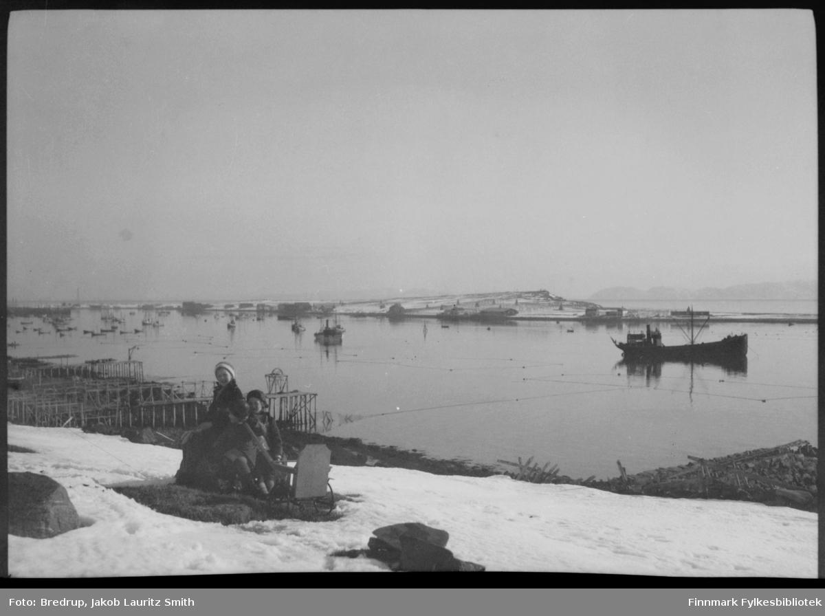 Vadsø havn fotografert fra vest.  Man ser hele Vadsøya og båter og garnlenker på havna.  Midt i bildet sitter tre småjenter på en stein med ei lekekjerre mellom seg.  Det er en blikkstille vårdag.