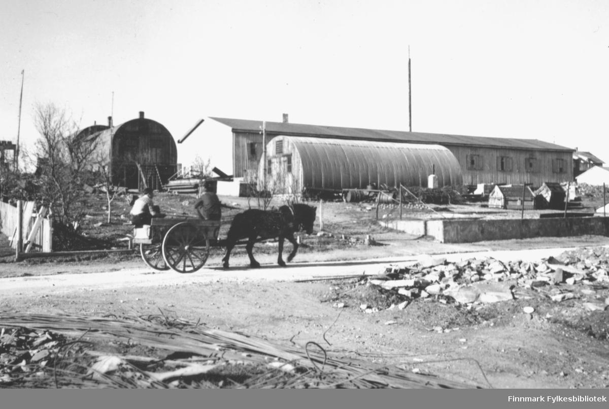 Hest og kjerre med to mann kjører forbi brannstasjonen. I bakgrunnen står flere brakker, blant annet hotellbrakka. I forgrunnen ligger ruiner