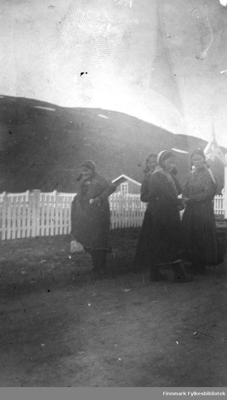 Fire samiske kvinner fotografert utenfor kirka på Langnes i Tana i 1916. Originalbildet var svært bleket, så den digitale kopien er noe utydelig