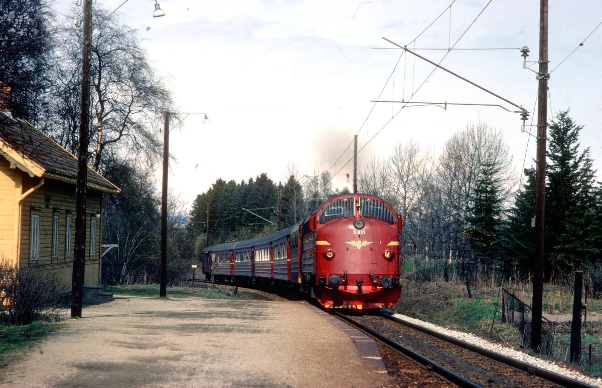Rørosbanens dagtog, tog 302, passerer Stavne holdeplass i Trondheim. NSB dieselelektrisk lokomotiv Di 3 611 trekker toget.