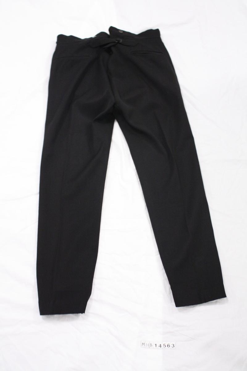 Bukse til brannkonstabel uniform. Sort med rød stripe vertikalt lang buksebeinet. Mulighet til å spenne inn bak på bukselinningen. To lommer på baksiden samt to lommer i siden. Slitefor på innsiden i bukselinning.