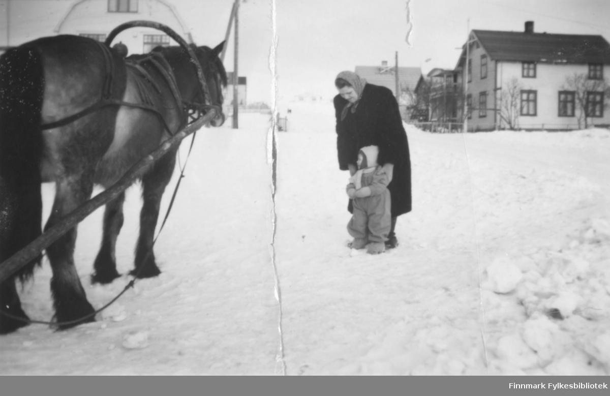 Bestemor Svanhild Kvam sammen med datterdatteren Torill i 1951, de står sammen og ser på en stor hest. Det ser ut til at bygningene i bakgrunnen ligger i Oscarsgate