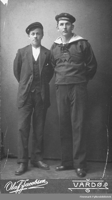 Visittkortportrett: To ukjente unge menn fotografert i Vardø. Mannen til høyre er kledd som sjømann, og lua er merket med fartøyets navn - 'Frithjof'