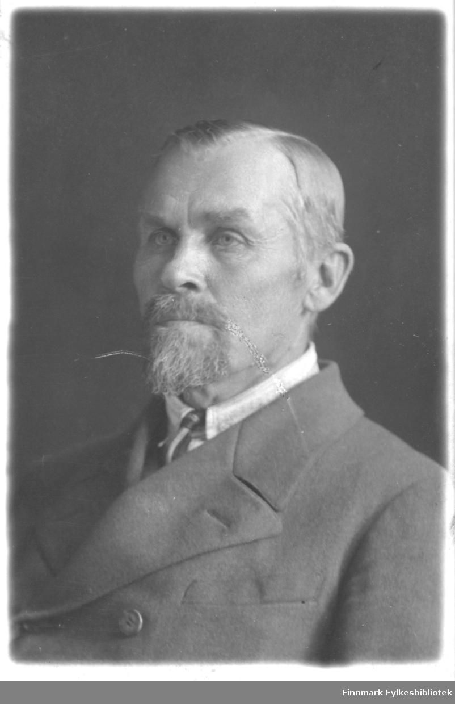 Portrett av eldre mann, ikke identifisert. Mannen er kledd i dobbeltspent dress med slips.