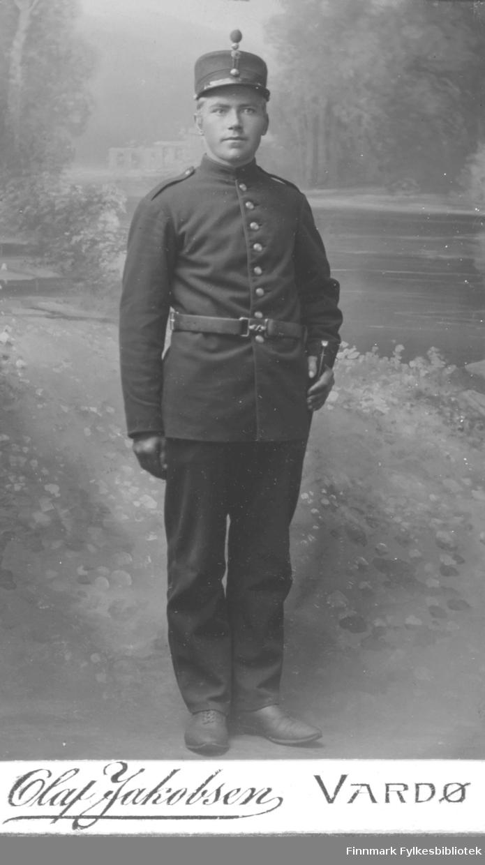 Portrett av ukjent ung mann i infanteriuniform.Uniformen består av en hatt, jakke, sko, belte, hansker og bukser. Bildet er tatt i Vardø og man kan kanskje anta at mannen tilhører Vardøhus festning? Fotografert av Olaf Jakobsen, Vardø.