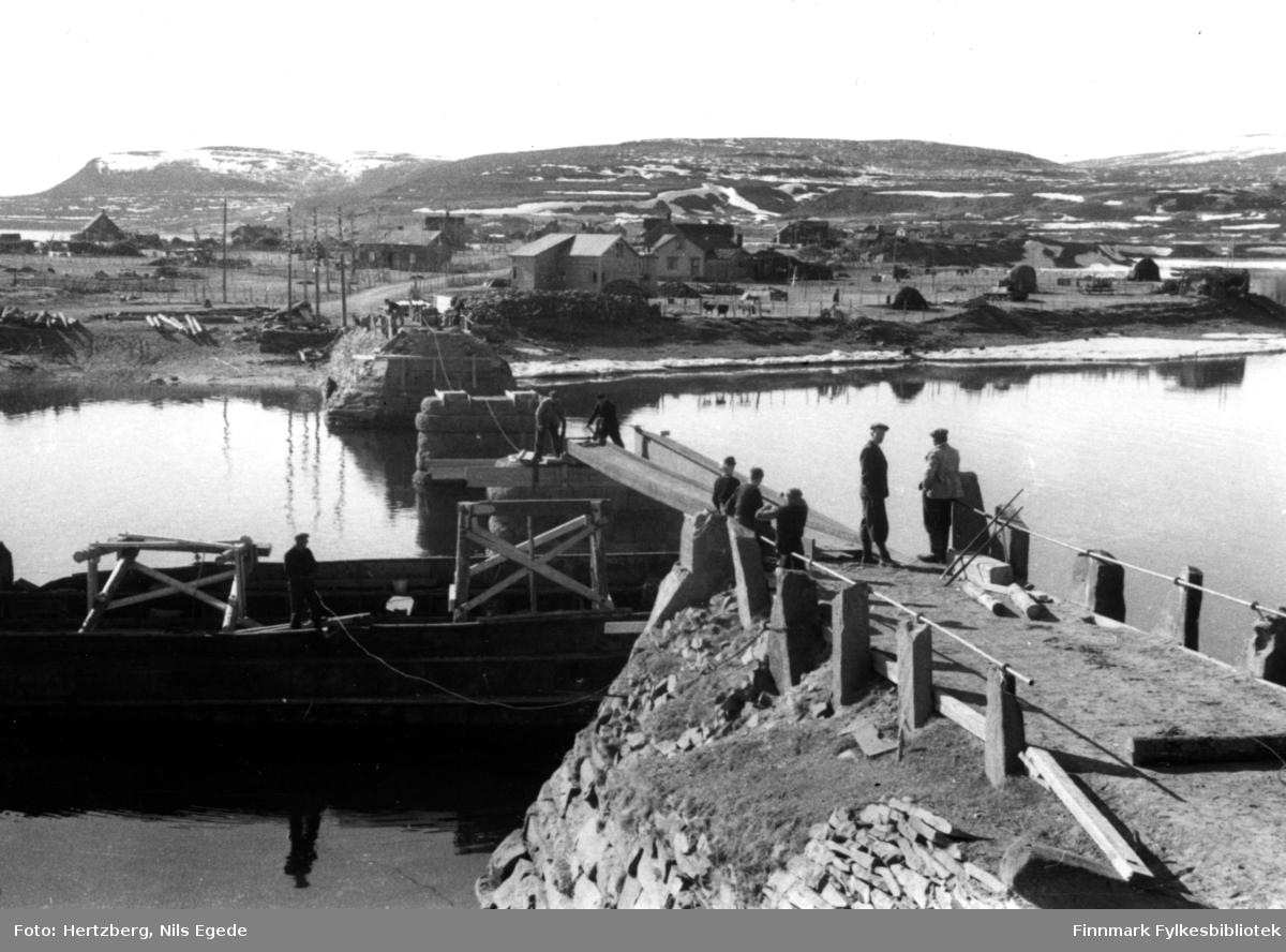 Brubygging i Vestre Jakobselv. En båt ligger under bruen. En mann er ombord i båten. Fire menn jobber på bruen. Tre gutter står å ser på arbeidet. I bakgrunnen ser man noen hus.