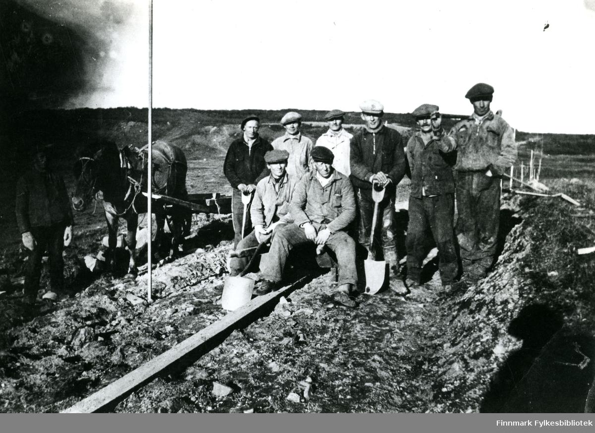 Bildet viser et arbeidslag på ni personer og en hest. Bildet er tatt på strekningen Karlebotn - Gandvik. Stående fra venstre ser vi; nr.2 Mathis Mathisen, nr.5 Klemet Mosesen, nr.7 Mathis Persen. Sittende foran; nr.2 Iver Persen