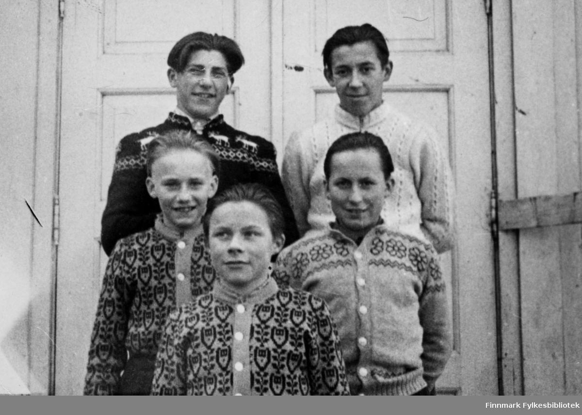 """""""Brylkremgutta"""" stiller til fotografering utenfor skoleinternatet på Skjånes, ved inngangen til gymnastikksalen. Der fantes også et lite kontor under galleriet, som ble brukt som tannlegekontor. En trapp førte opp til klokketårnet. Skolen var nemlig en gang bygget som skolekapell. Bildet kan være tatt i tidsperioden 1950-51.  Oppe fra venstre: Bjørn Nikolaisen, Arnold Nilsen, Ragnar Persen, Emil Corneliussen, Odin Bavda"""