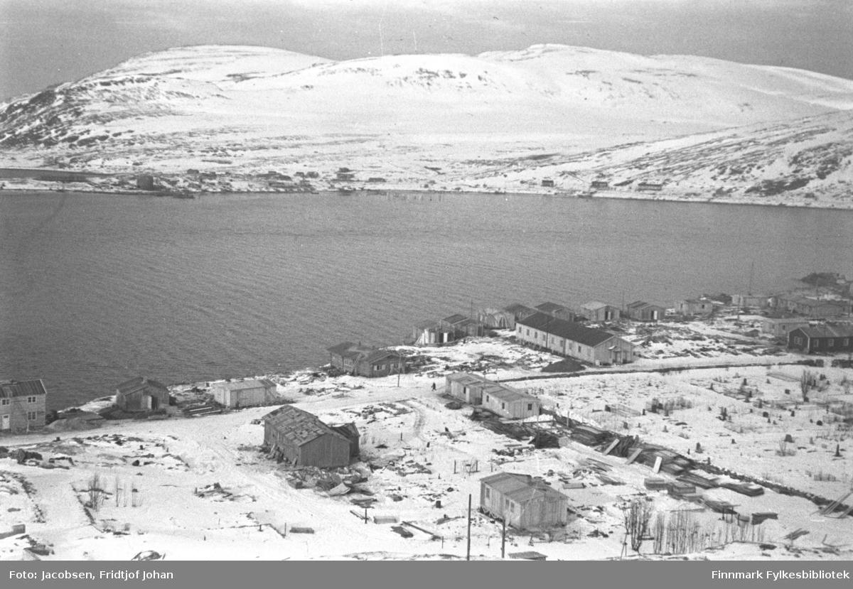 Bydelen Haugen i Hammerfest, høst/vinter 1945. Den lange, lyse brakka like nedenfor kirkegården, var FFR-brakka. Der FFR-brakka lå står i dag Hammerfest kirke. Gravlunden ligger til høyre i bildet og muren går langsmed der hvor FFR-brakka står. Noen flere brakker er satt opp på området som er delvis snødekt, men en del ruiner ses også. På andre siden av havna ligger bydelen Fuglenes. Noen brakker er satt opp der og, og saltsiloen ses ute på Fuglenesodden til venstre på bildet. Fjellet til venstre på bildet er Vardfjell med toppen av Vedhammeren bak. Midt på bildet er Storfjellet med Fuglenesdalen nedenfor.