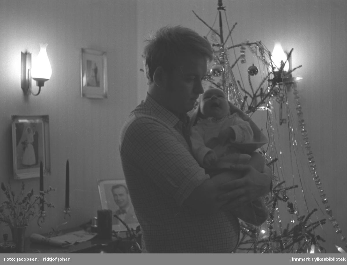 Bildet viser en mann som holder et spedbarn. Mannen kan være Halvard Sebergsen, med datteren Sissel. Han har en rutet, kortermet skjorte på seg. Barnet har en lys drakt og er pakket inn i et teppe. Et juletre står ved siden av dem, inntil en vegg der en lampe henger. Bak dem står en kommode/hylle med et fotografi, en lysestake og en blomstervase stående oppå. To brudebilder henger på veggen over kommoden/hylla.