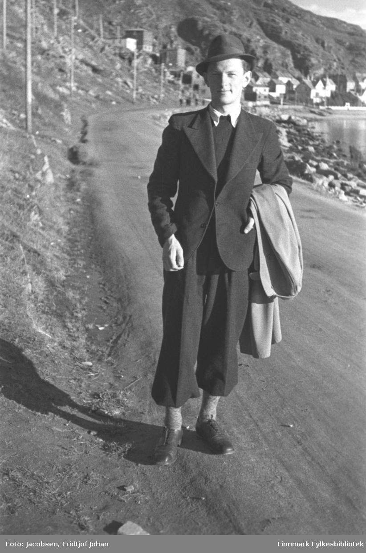 Ragnvald Jacobsen på Fuglenesveien. Han er iført en mørk dress med hvit skjorte og har en mørk hatt på hodet og mørke sko. Han har også forholdsvis lyse stømper og frakk hengende over sin venstre arm. Fuglenesveien har grusdekke og el-stolper står på ene siden og fjæra ses på andre siden. Bebyggelsen i bydelen Molla ses i bak på bildet med Mollafjell i bakgrunnen.