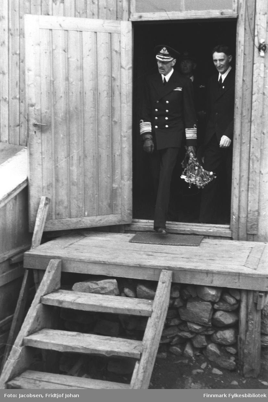Kong Haakon VII på vei ut av lensmannsbrakka. Bildet er tatt under kongebesøket 10 juli. Han har uniform på seg og en blomsterbukett i sin venstrehånd. Litt bak han står en mann mørk dress og litt i bakgrunnen ses en mann i mørk uniform. Brakka er satt opp på en mur av stein og en liten matte ligger foran døra. Døra er kilt fast med en planke for å holde den åpen.