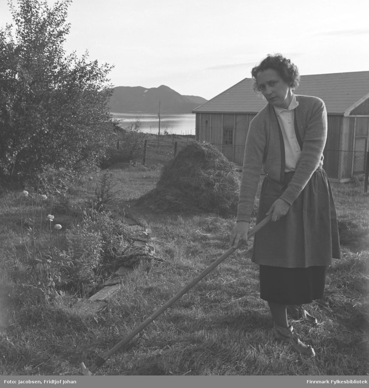 Aase Jacobsen raker gresset på eiendommen til sin far Arne Nakken. Hun er iført ganske lyse klær med skaller på beina. En stor haug med gress ligger litt bak henne og et løvtre står til venstre på bildet. Et blomsterbed med noen blomster i ses foran treet. En bygning og et gjerde ses i bakgrunnen. Fjellet som ses helt bakerst på bildet er Seiland.