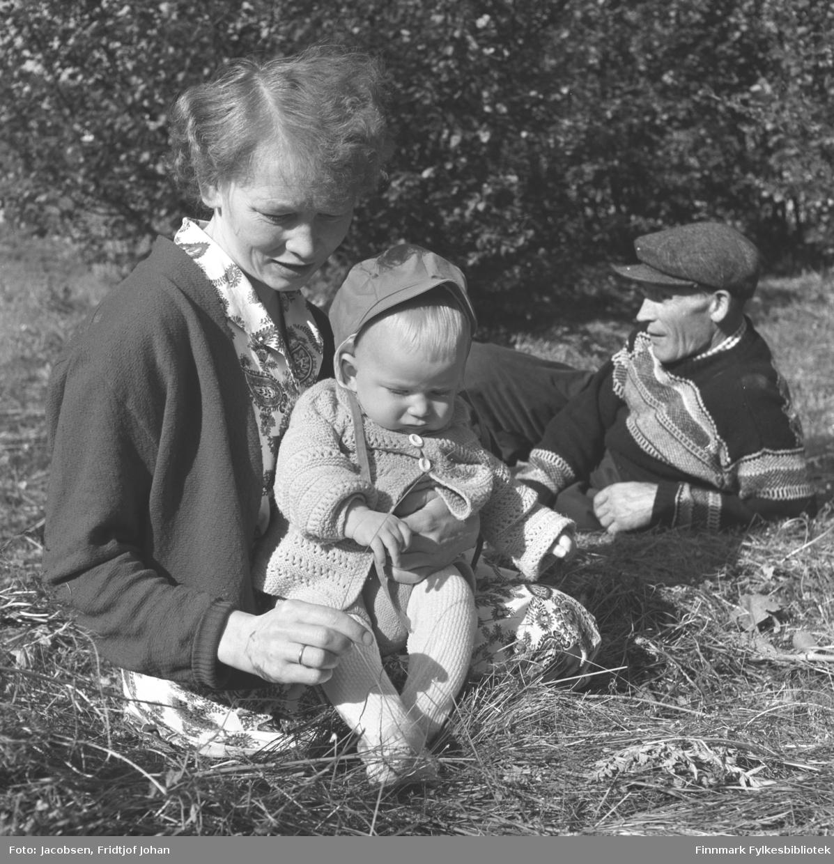 Sommer i Hammerfest. Henriette Nakken med sønnen Sigmund på fanget. Hun har en lys kjole med mønster og en mørk jakke på seg. Arne Nakken ligger avslappet i gresset bak dem. Han har en mørk genser med striper og en skyggelue på hodet. Sigmund har en lys strømpebukse og en litt mørkere heklet jakke på seg. Noe gress og litt løv ligger på bakken foran dem og ganske tett med bjørketrær står litt bak dem.