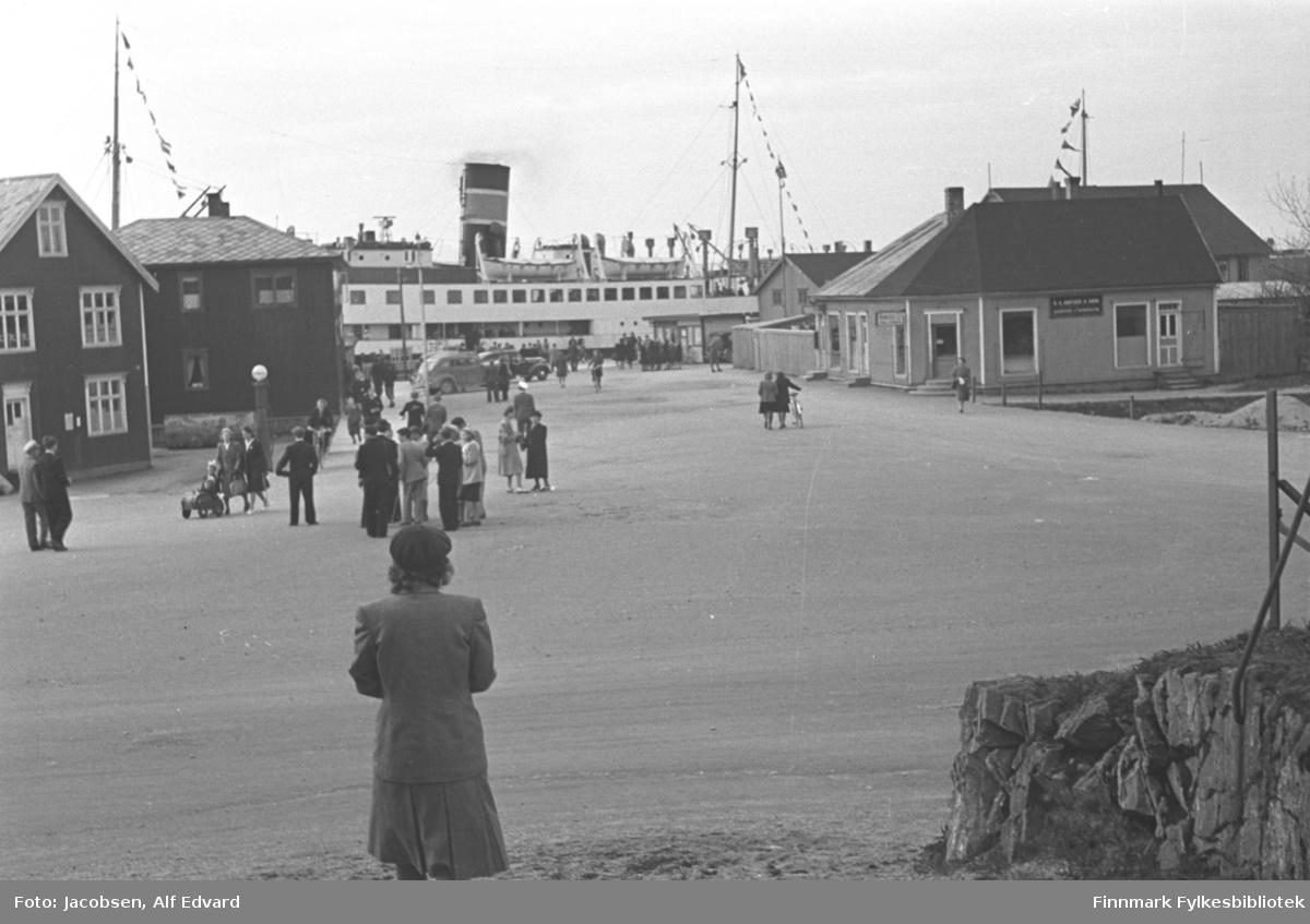 """Dampskipet DS """"Lofoten"""" liggende ved kai i Brønnøysund. Bare midtre del av fartøyet ses mellom bygningene. På øverste dekk henger to livbåter. Begge mastene ses med flagg/vimpler hengende i tau fra toppen og ned mot dekk. Den svarte skorsteinen står mellom mastene og har en påmalt stripe. Til venstre på bildet står to mørke bygninger. Begge har skiferdekke på taket og det helt til venstre har sprossevinduer med hvite karmer. En lys dør står nede på røstveggen. Til høyre på bildet er tre bygninger. Det nærmeste er ganske lyst, har store vinduer og et skilt på veggen, muligens en forretning. En dør står nede på langveggen og bygget har pappdekke på det valmete taket. Et gjerde går fra hjørnet og ned mot Hurtigruta. Bak det ses to andre bygninger, et ganske stort og et mindre. En stor, åpen plass foran og midt på bildet. En del mennesker er på området. En barnevogn og en sykkel ses også. To biler står parkert nederst på kaia. Nede til høyre på bildet er en liten del av en stein/steinmur og noen tynne stolper ses oppå."""