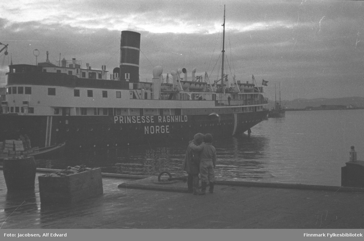 Hurtigruteskipet Prinsesse Ragnhild ligger ved dampskipskaia. Skroget er sort-malt med hvitt overbygg. Deler av overbygget på rorhuset er mørkt og skorsteinen også med en påmalt stripe. Et par personer ses på dekk. Nesten på hekken står en av mastene, bardunert mot rekka. Helt på hekken henger det norske flagget fra en skråstilt flaggstang. Bak Hurtigruta ligger en båt på havna. Båten er ganske mørk, har et høyt avlangt rorhus og to master. Ved baugen på Hurtigruta ligger et mindre fartøy med to kassestabler på dekk. Kassene lastes eller losses fra Hurtigruta. På andre siden av den blikkstille havna ses Fuglenesodden og noe diffust bak odden ses Sørøya. Nærmest kamera står to små gutter. De står på kanten av Kjølelagerkaia. Begge har støvler og gutten til høyre har forholdsvis lyse klær på seg. Han holder armen rundt skuldrene på gutten ved siden av seg som har litt mørkere klær på seg. Ved siden av dem er en fortøyningsring støpt i kaia.  To kasser med div. saker oppi står på kaia helt til venstre på bildet. Det er ganske tett skylag på himmelen