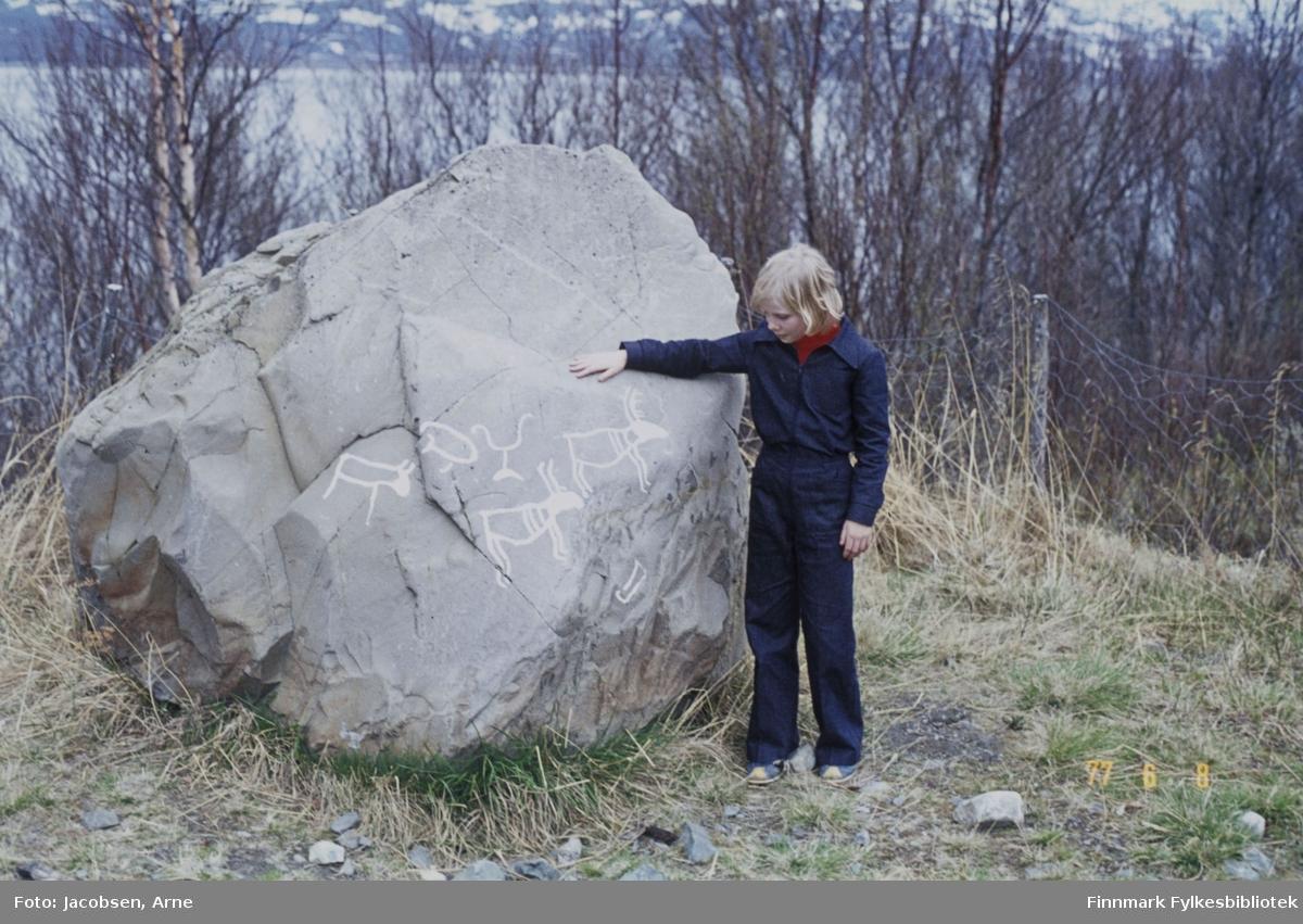 Arne Jacobsens datter Laila Stenmann står ved siden av en stor stein med helleristningsmotiv på. Steinen ligger fritt i terrenget og på bakken rundt den er det gress. Laila har mørk bukse og mørk overdel på seg og holder en hånd på steinen. Bak den står et netting-gjerde og mye trær. På andre siden av vannet ses et snøflekket landskap.