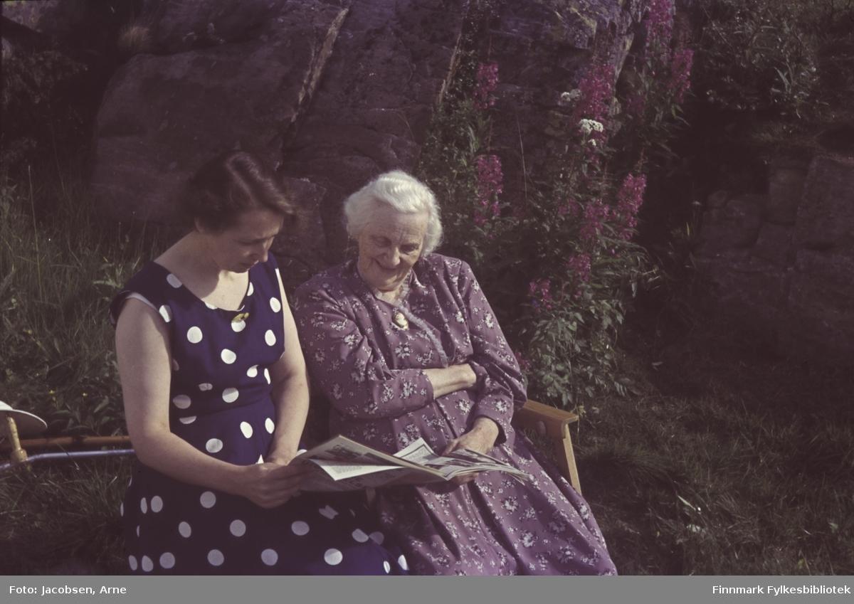 To damer, Alfhild og Olga Jacobsen, sitter i solskinnet foran en stor bergknaus. Olga sitter i en stol og har en blomsterfarge kjole på. Alfhild sitter på bakken i en kortermet, mørk kjole med lyse prikker. De leser i en avis eller et tidsskrift og stokk eller krykker ligger i gresset rett bak dem. Noen blomster står foran berget og til høyre er steiner stablet opp til en liten mur som det står en liten busk på.