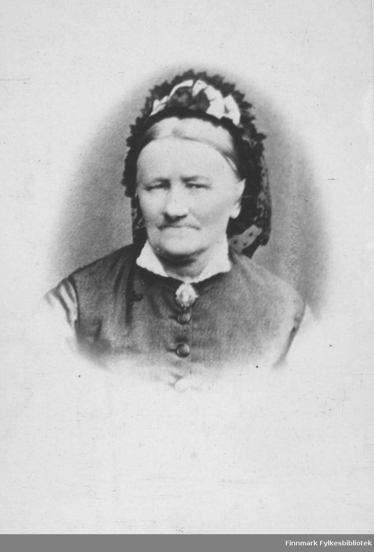 Portrett av Henrikke Vibe. Døde 1892 i Vardø. Hun var mor til Anna Christine Vibe Jacobsen, som var gift med smedmester i Vardø Ole Sigfrid Jacobsen. På bildet er hun kledt i hvit skjorte og vest. Hun har en brosje som pynt i halsen. På hodet har hun et pyntetørkle